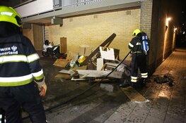 Brandweer blust stapel grofvuil tegen muur van flat